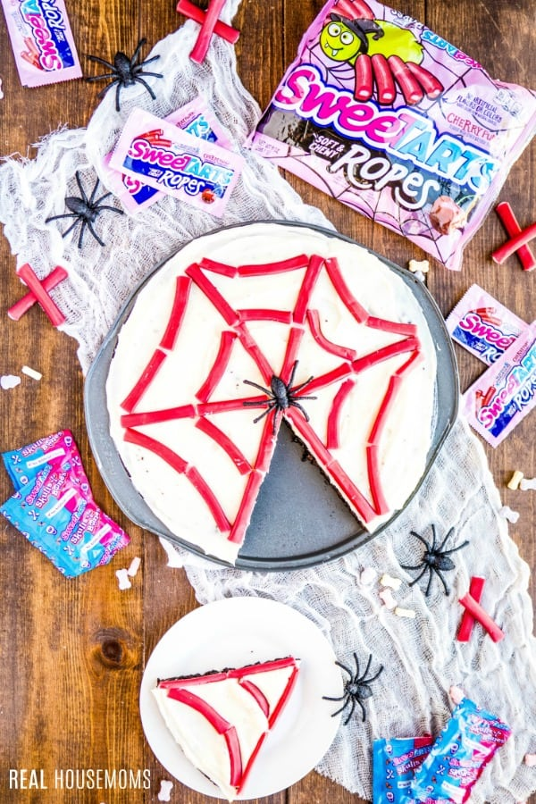 spider web brownie pizza on a tray with SweeTARTS candies and slices around