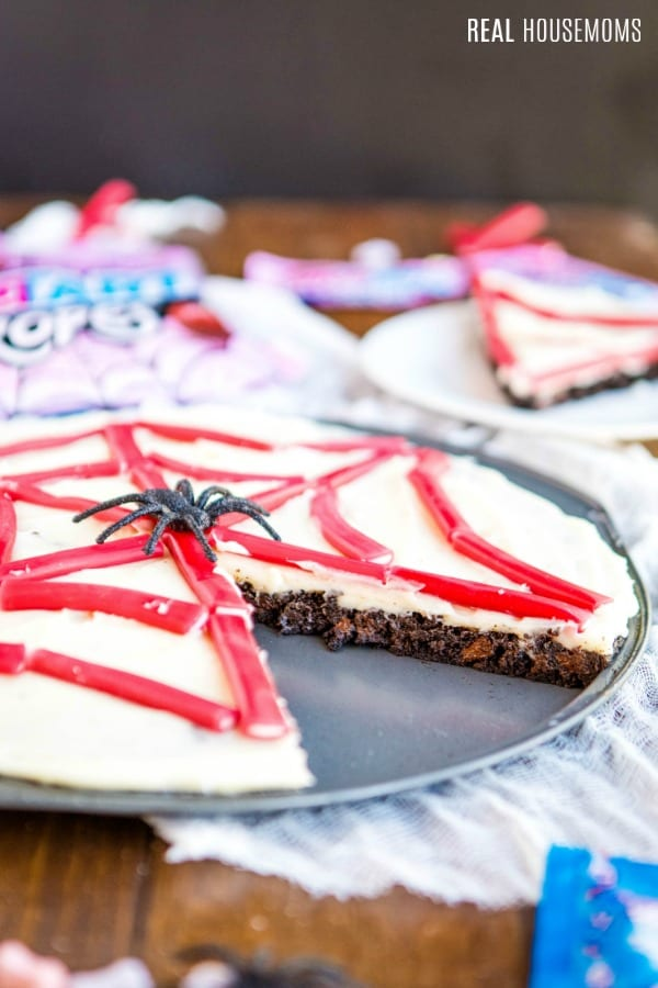 spider web brownie pizza with a slice cut out