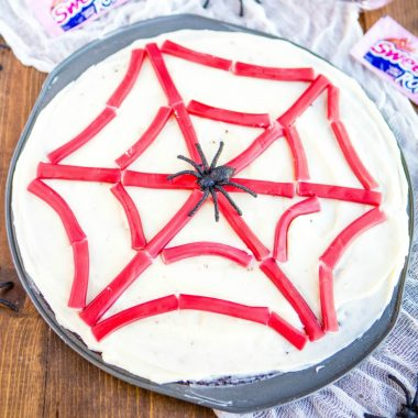 Spider Web Brownie Pizza is an easy dessert that'll be the talk of your Halloween party!! It's loaded with cream cheese frosting, SweeTARTS Ropes & spiders!
