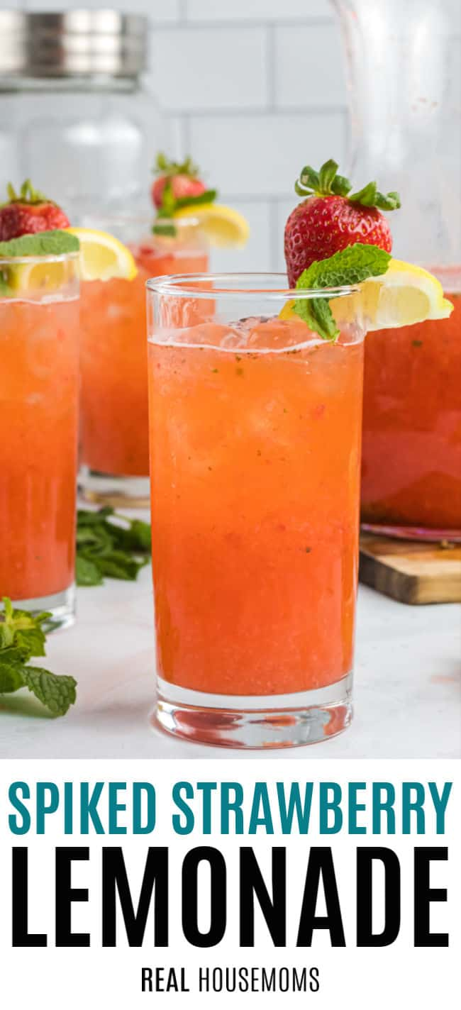 glass of spiked strawberry lemonade garnished with a lemon wedge, mint leaf, and strawberry