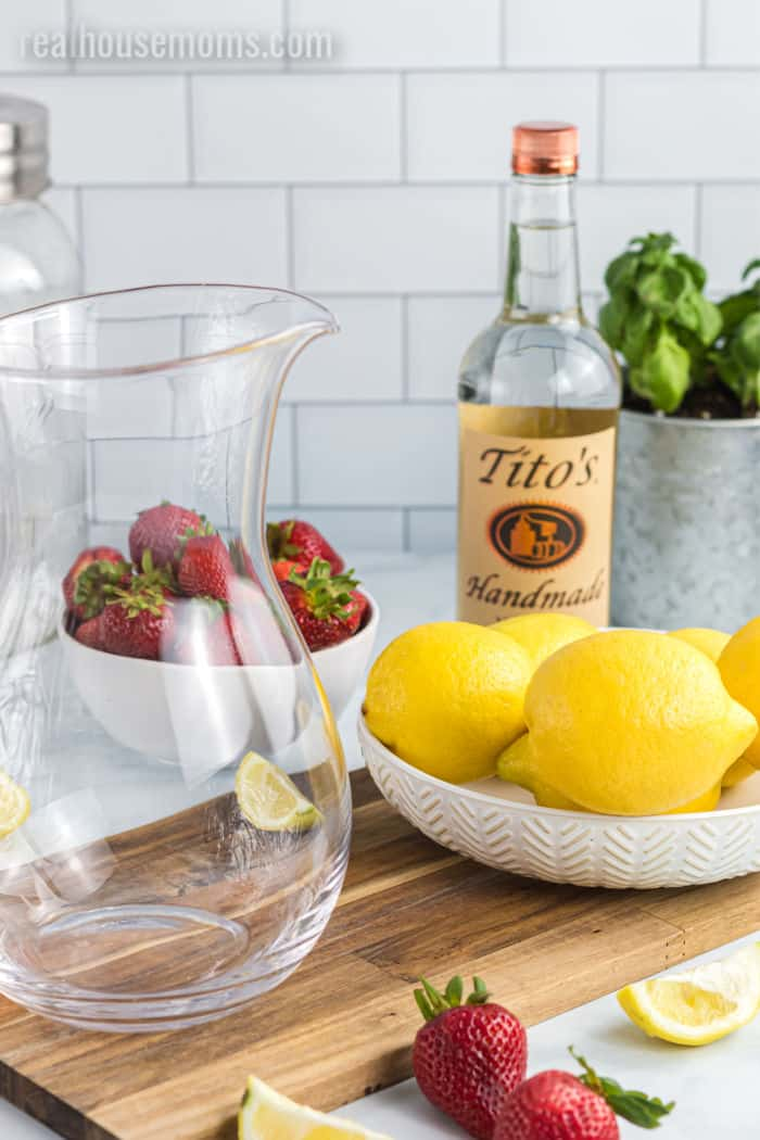 empty pitcher, bottle of Tito's vodka, strawberries, lemon, and mint sitting on a cutting board