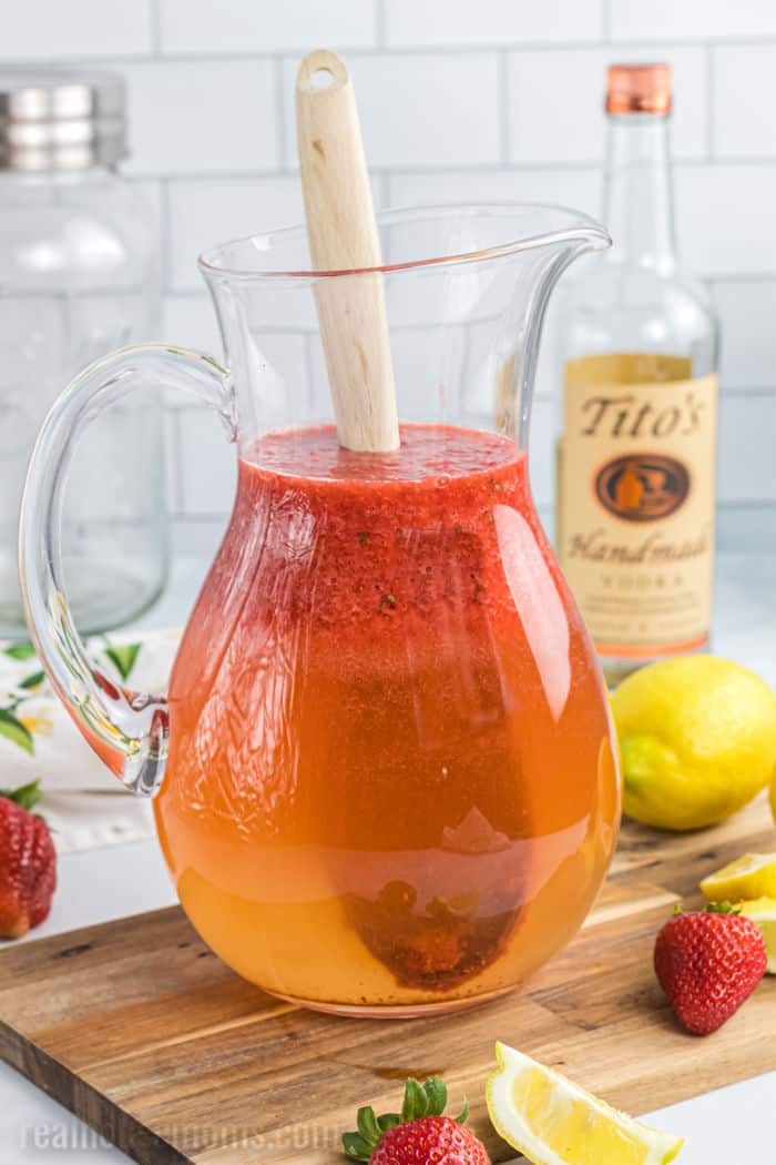 vodka, simply syrup, and water in a pitcher topped with strawberry puree and a wooden spoon