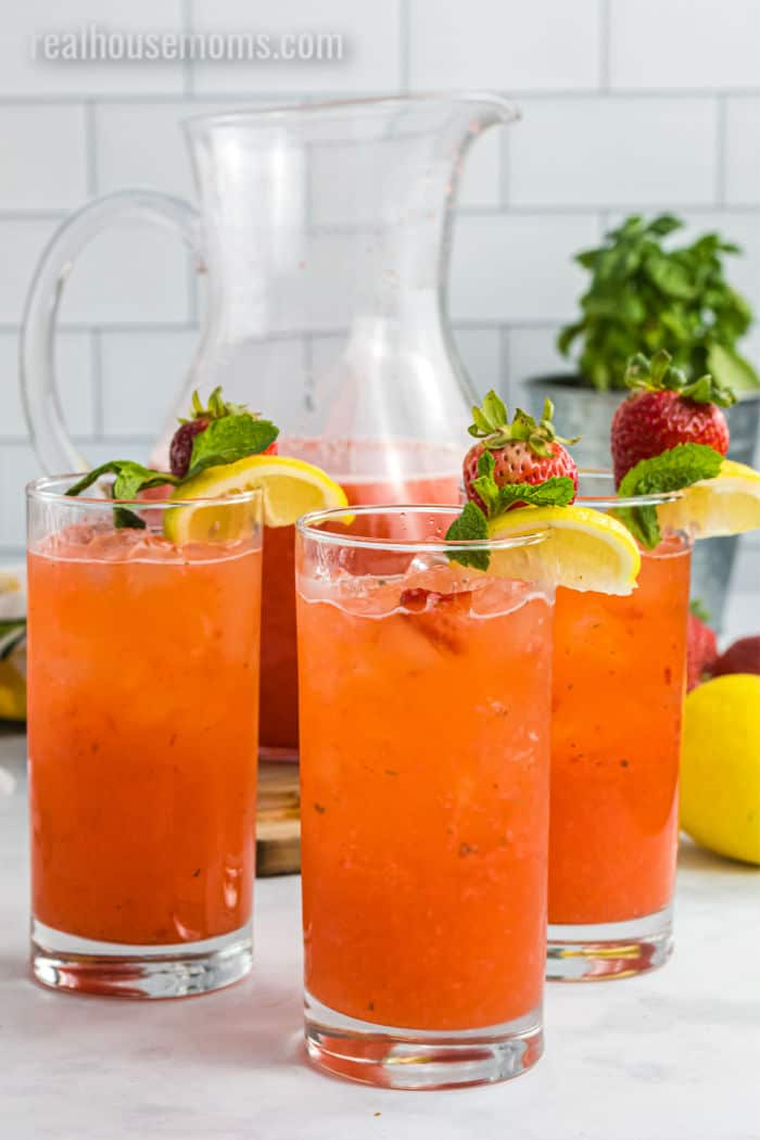 three glasses of spiked strawberry lemonade with a pitcher of the cocktail