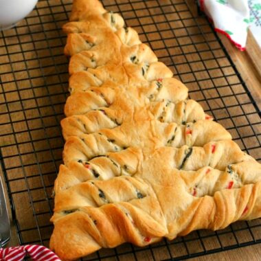 square img of spinach dip stuffed crescent roll Christmas tree on a wire rack