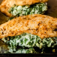 three spinach stuffed chicken breasts on a baking sheet with recipe name at bottom