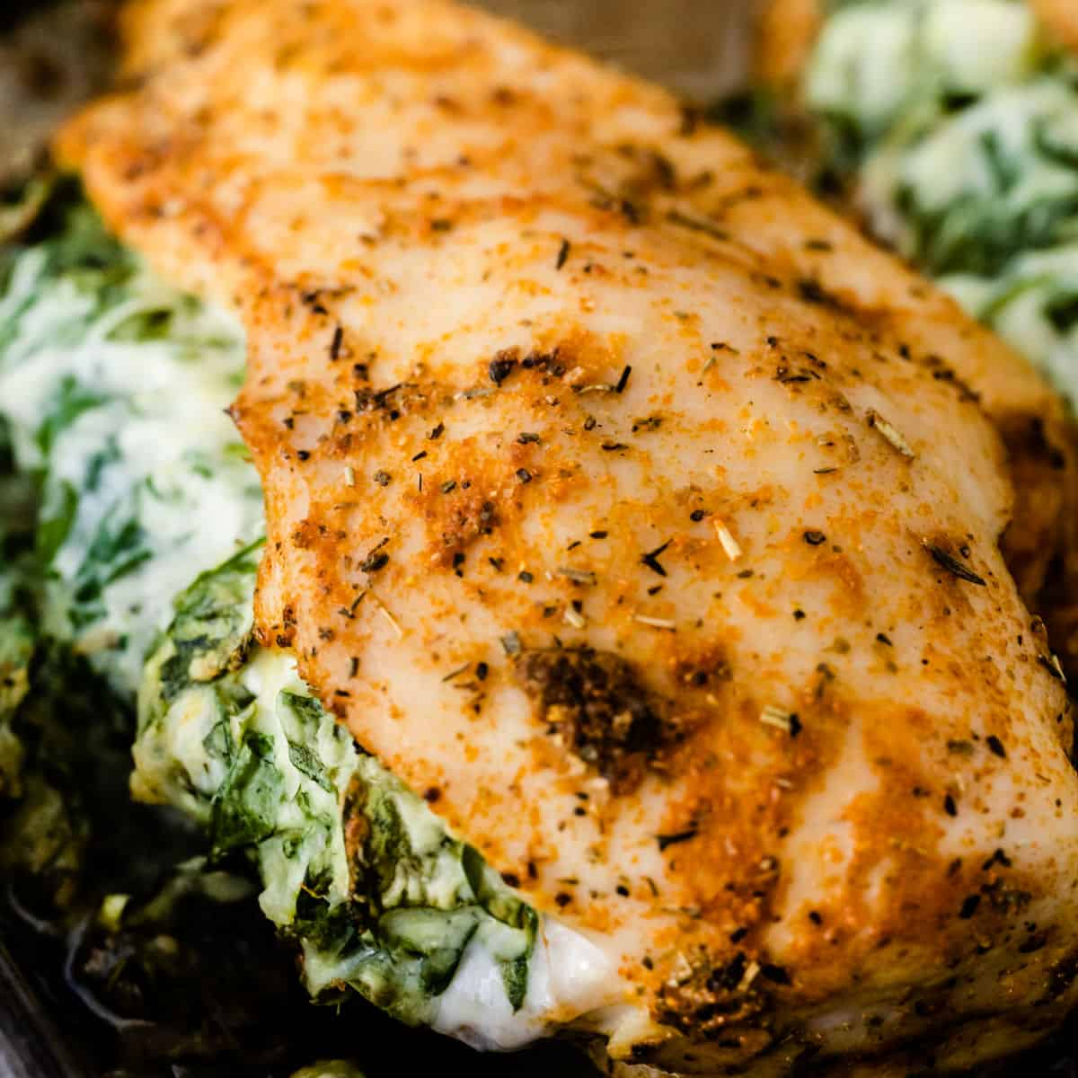 square image of spinach stuffed chicken on a baking sheet