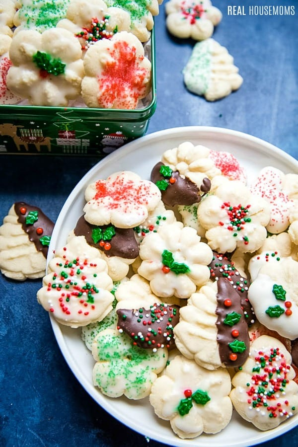 spritz cookies on a plate and in a tin for gifting