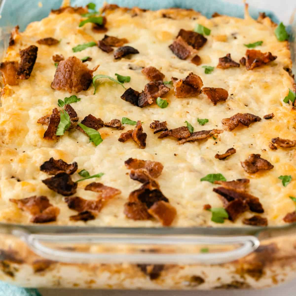 square image of sriracha ranch bacon chicken dip in a glass baking dish