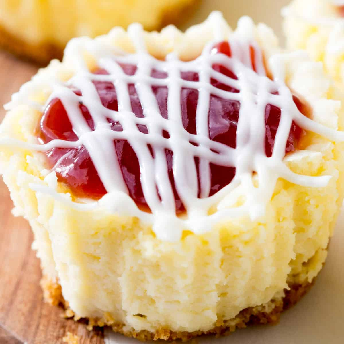 square image of mini strawberry cheesecake out of cupcake liner on a cutting board