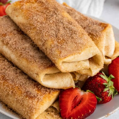 square image of strawberry cheesecake chimichangas piled on a plate with halved strawberries