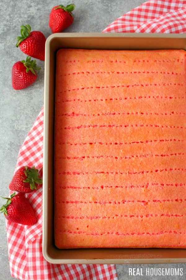 strawberry jello cake with holes poked in the cake and jello poured over the top