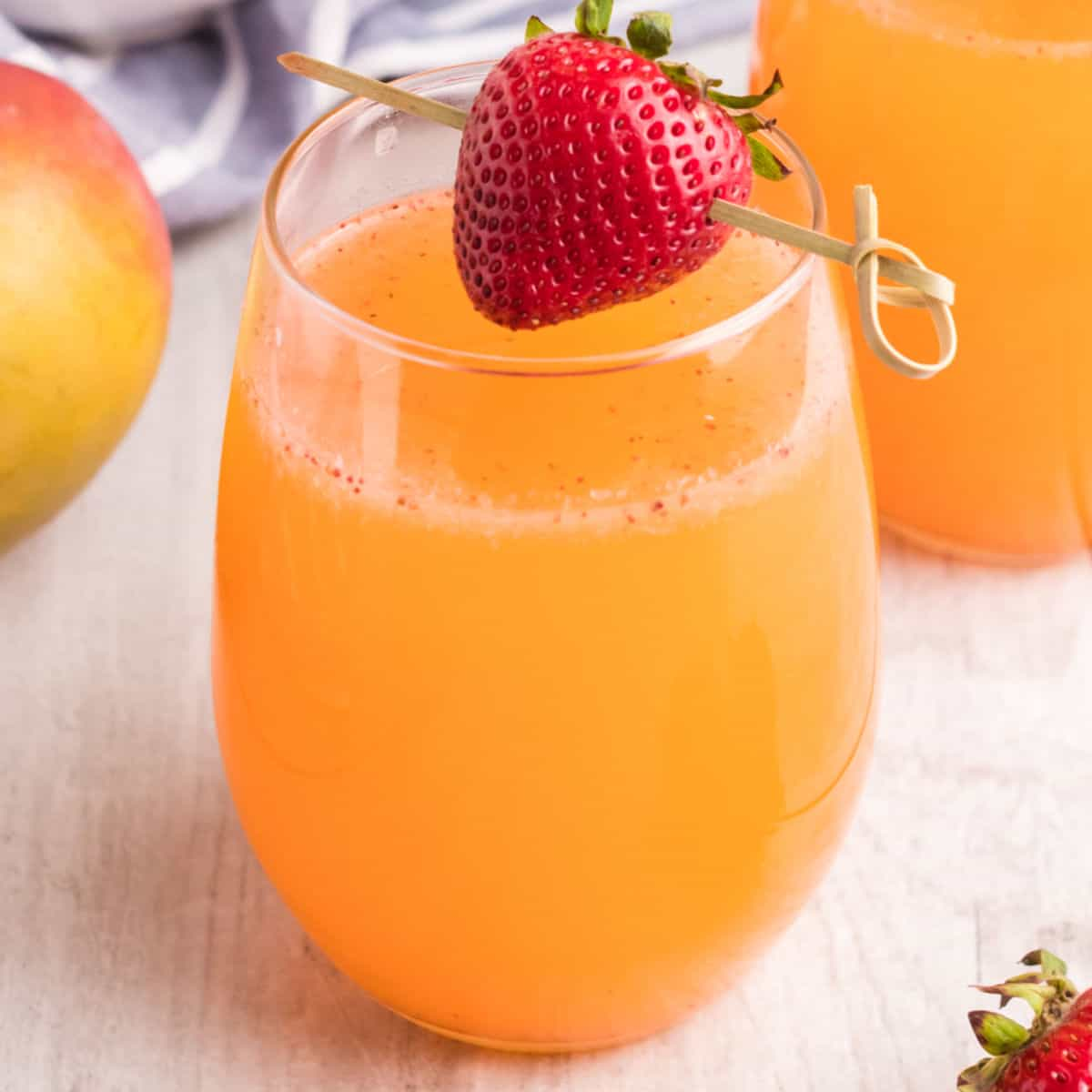square images of strawberry mango moscato punch in stemless wine glasses with a strawberry for garnish