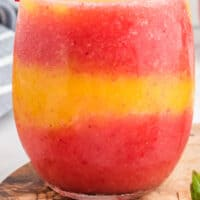 stemless wine glass with layers of Strawberry Mango Moscato Slushie with recipe name at bottom