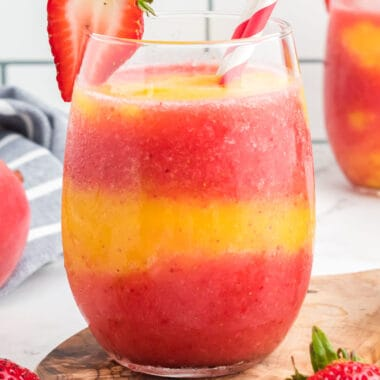 square image of a Strawberry Mango Moscato Slushie in a stemless wineglass with a straw and strawberry