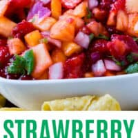 strawberry pineapple salsa in a bowl with a lime wedge and two strawberry halves on top with recipe name at bottom