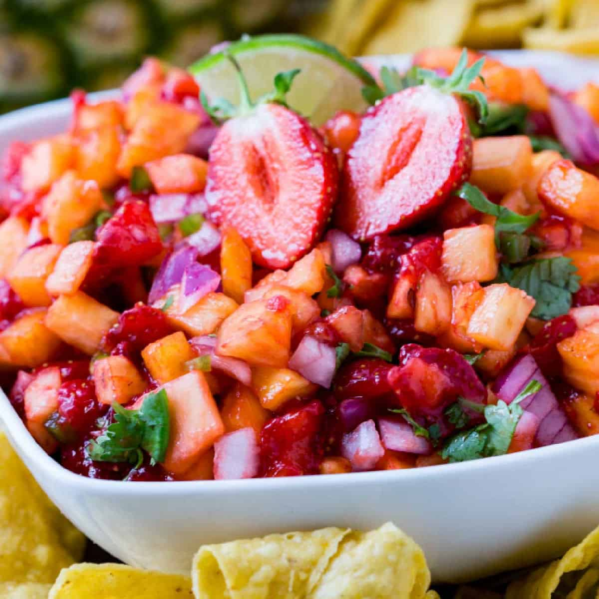 square close up image of strawberry pineapple salsa in a white bowl