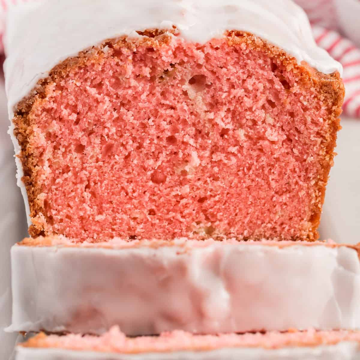 square image of loaf of strawberry pound cake with champagne glaze with slices cut to show inside