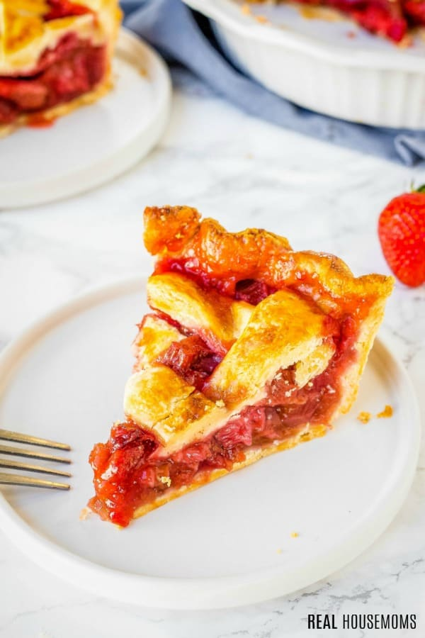 slice of strawberry rhubarb pie on a dessert plate with a fork
