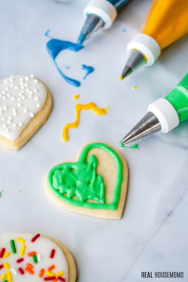 cut out cookie being decorated with sugar cookie icing