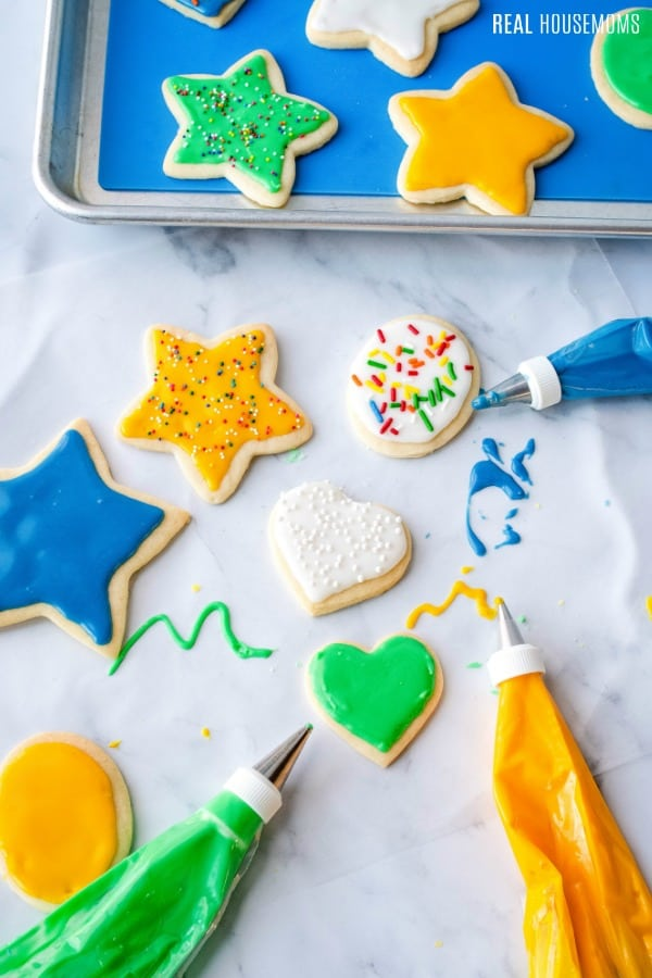 cut out cookies topped with sugar cookie icing and sprinkles