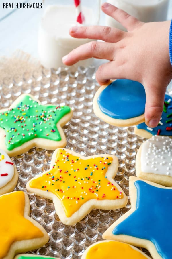 child's hand picking up a cookie topped with sugar cookie icing from a platter