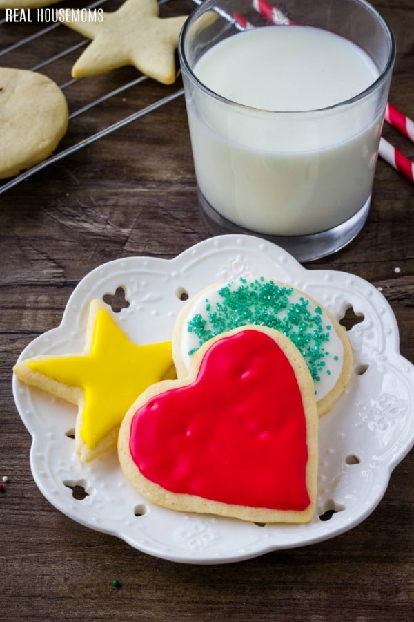 decorated sugar cookies on a dessert plate with a glass of milk