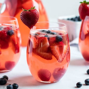 square image of summer berry sangria in a stemless wine glass
