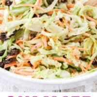 close up of summer coleslaw in a white serving bowl with recipe name at the bottom