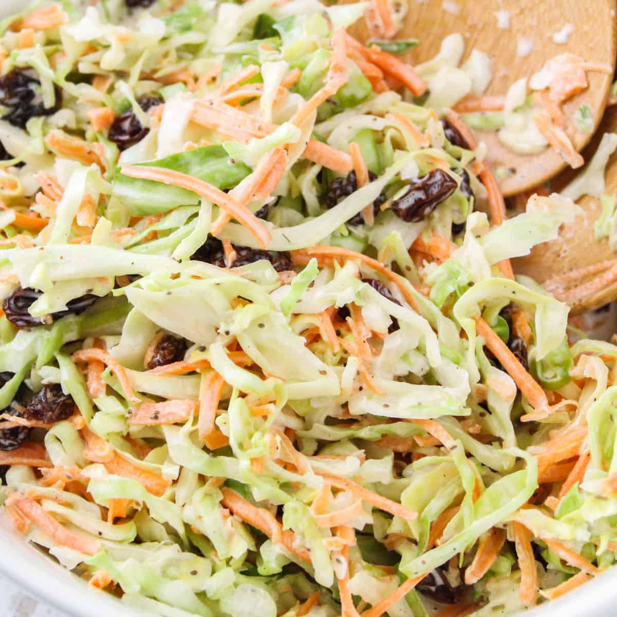 square close up image of summer coleslaw in a white serving bowl