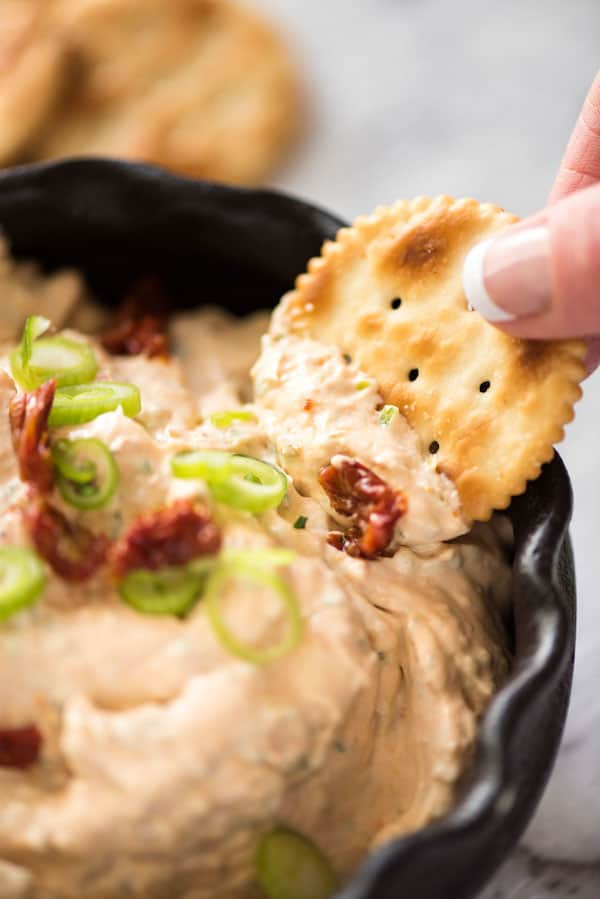Cracker that's been dipped into Sun Dried Tomato Dip