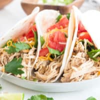 Super Easy Slow Cooker Chicken Tacos are the perfect weeknight meal! Let your crockpot do the hard work, then assemble your tacos and dig in!