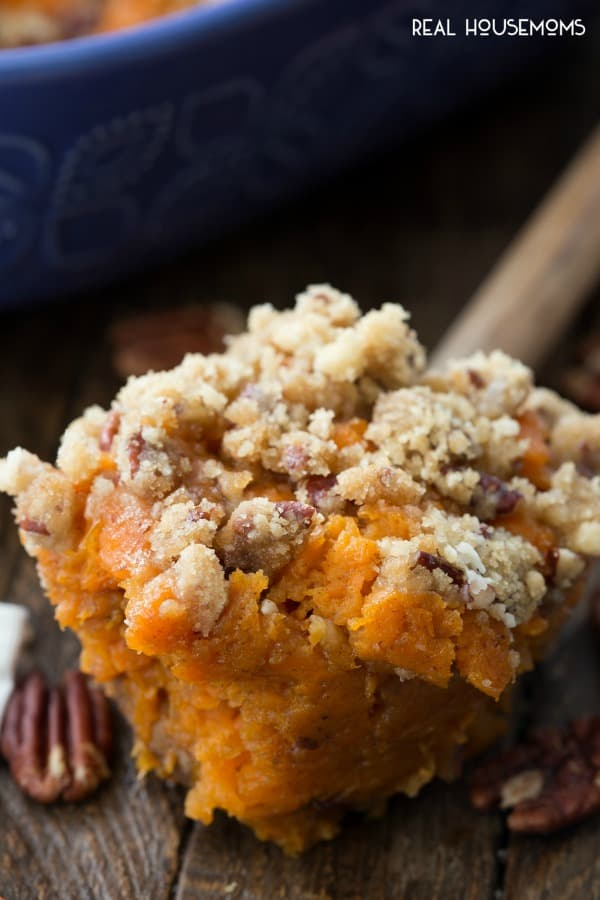 A big scoop of Sweet Potato Casserole on a wooden spoon