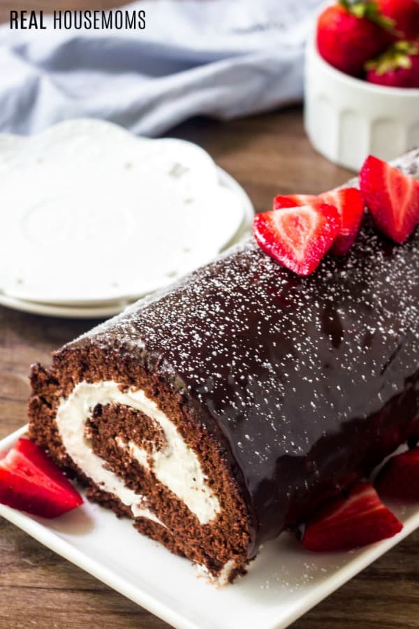 swiss roll cake glazed in chocolate ganache and topped with powdered sugar and strawberries