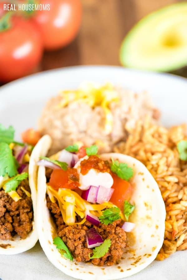 tacos on a plate with refried beans and rice