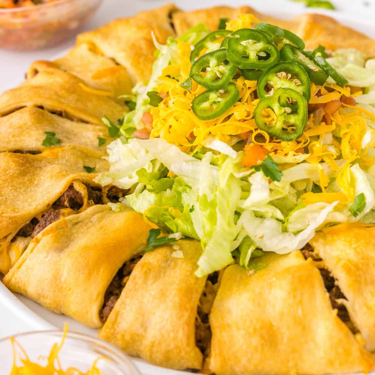 square image of taco crescent roll ring with lettuce, tomato, cheese, and jalapeno in the middle