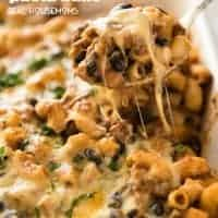 A spoon lifting Taco Mac N Cheese Pasta Bake out of the baking dish with gooey cheese pulling away