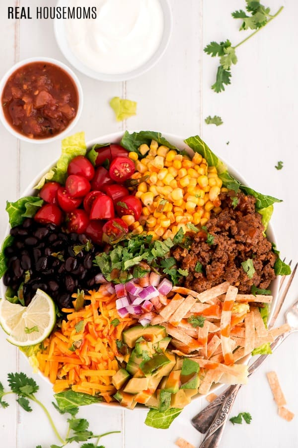 Taco salad ingredients in a bowl ready to be mixed