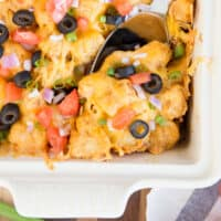 taco tater tot casserole with a serving spoon in the dish with recipe name at bottom