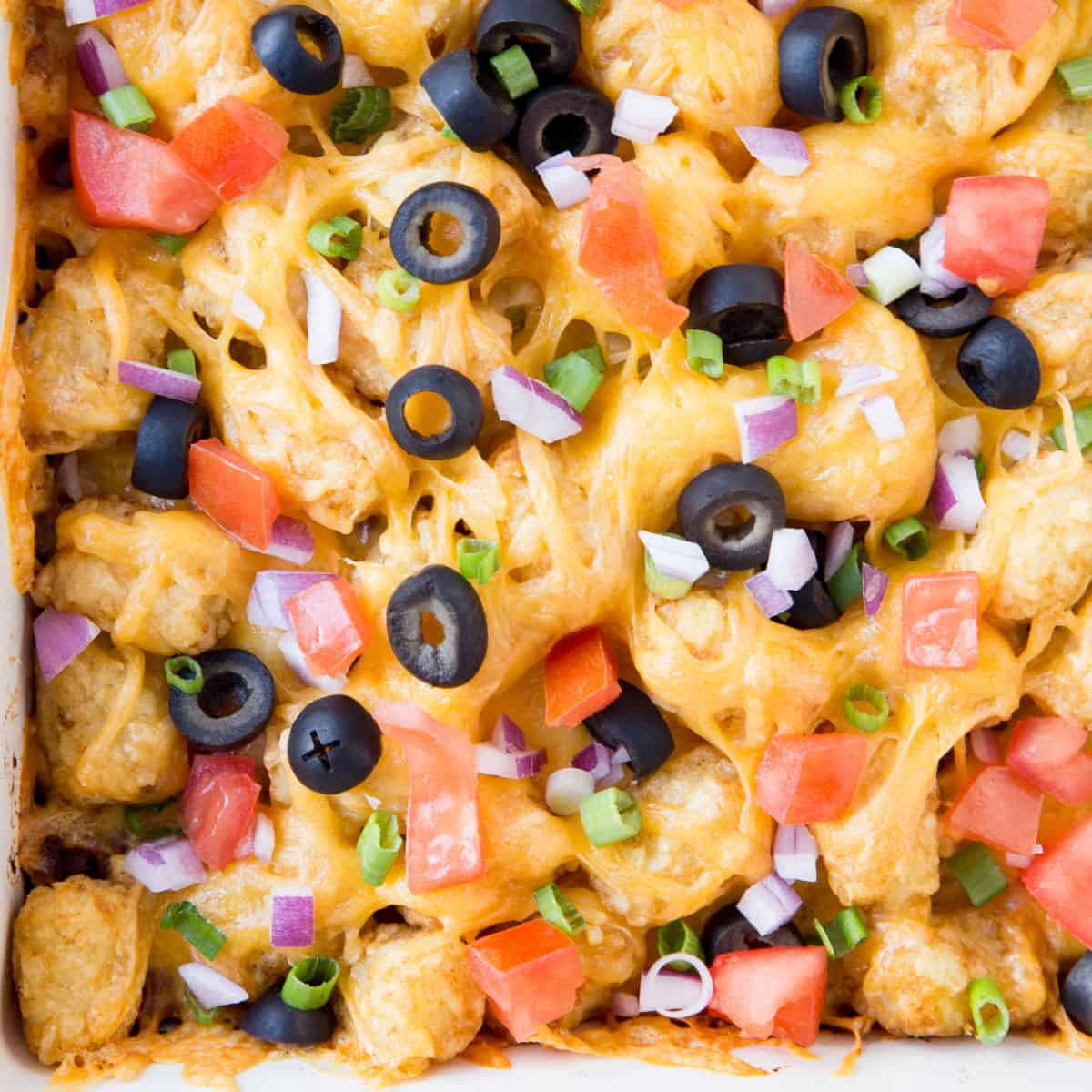 square close up image of taco tater tot casserole topped with tomatoes, red onion, and olives