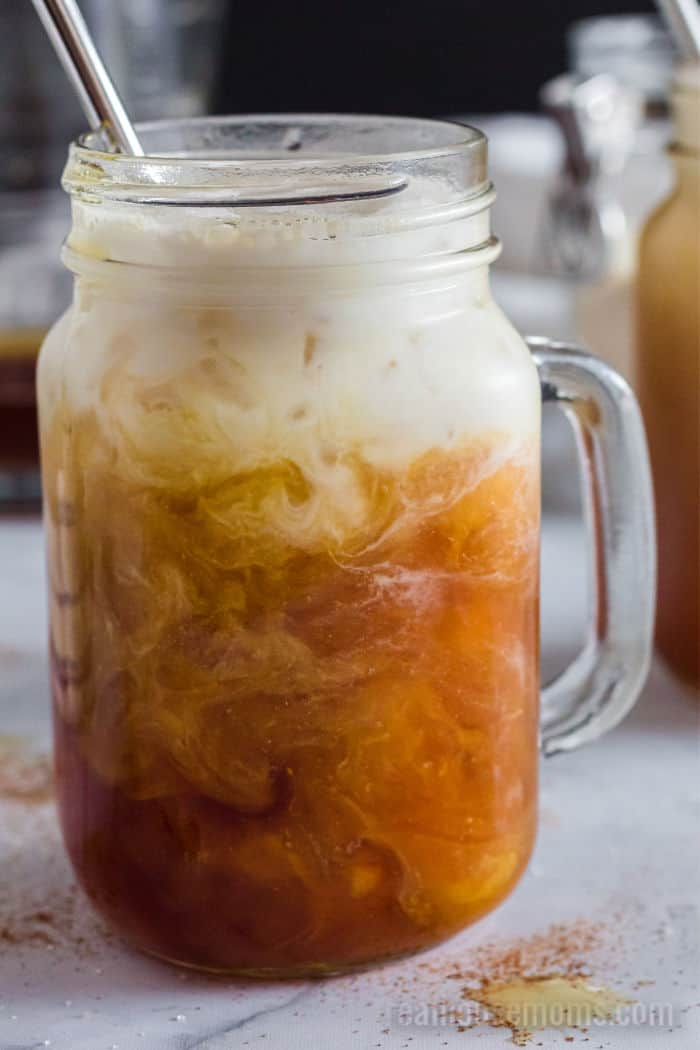coconut milk swirling into a glass of tea