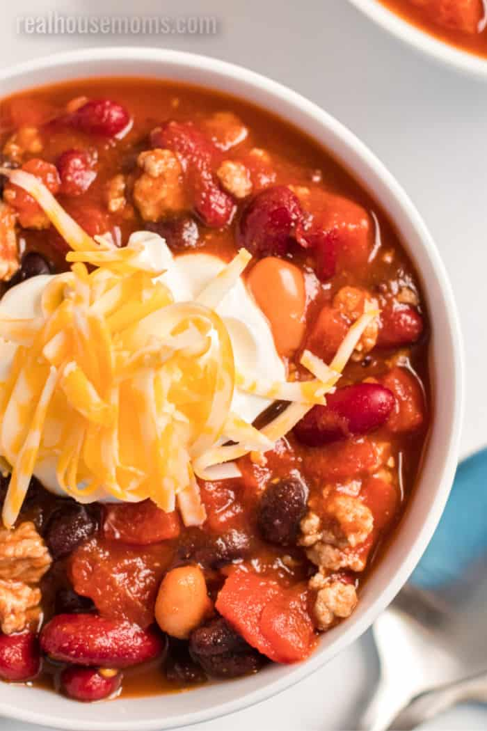 close up of a bowl of turkey chili with toppings
