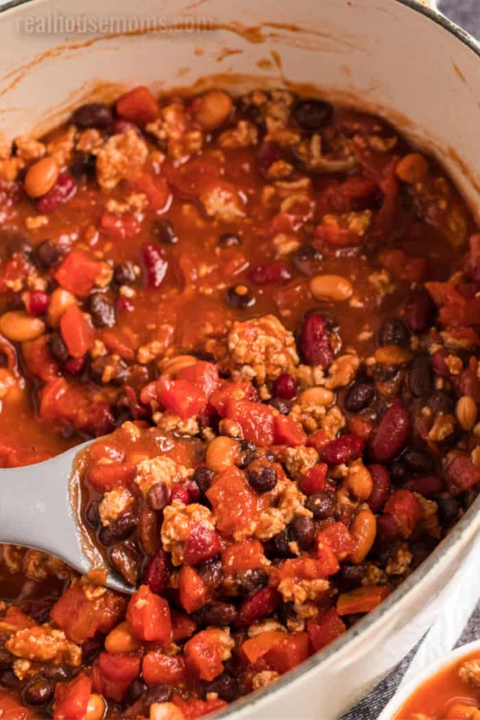 spoonful of three bean turkey chili over a pot