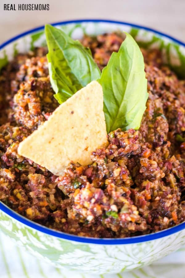 olive tapenade in a dip bowl with basil leaves and a tortilla chip