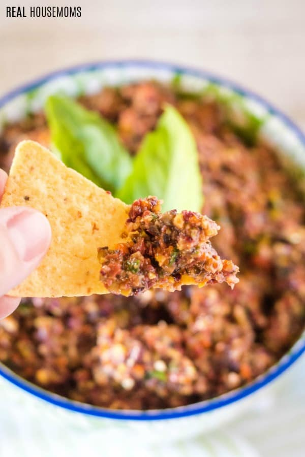 tortilla chip that has been dipped in olive tapenade