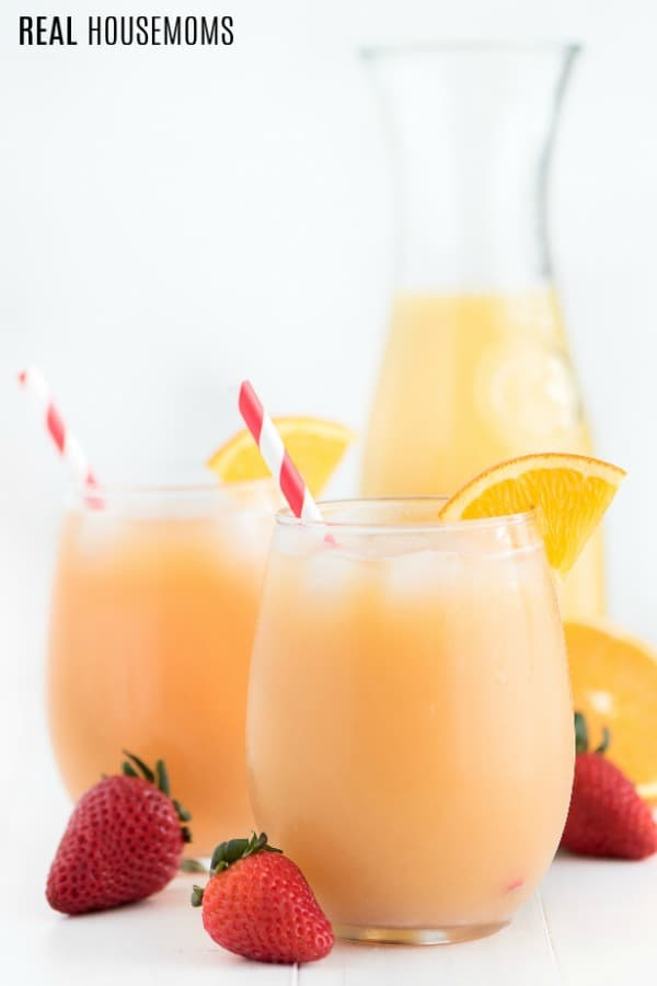 Tropical orange punch in glasses with straw and an orange slice