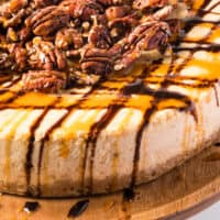 turtle pumpkin cheesecake on a wooden cake stand with recipe name at the bottom