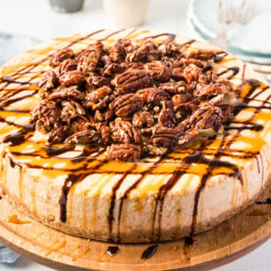 square image of turtle pumpkin cheesecake on a wooden cake stand