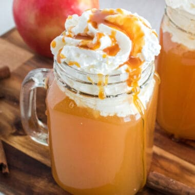 square image of warm apple cider in a mug with whipped cream and caramel on top