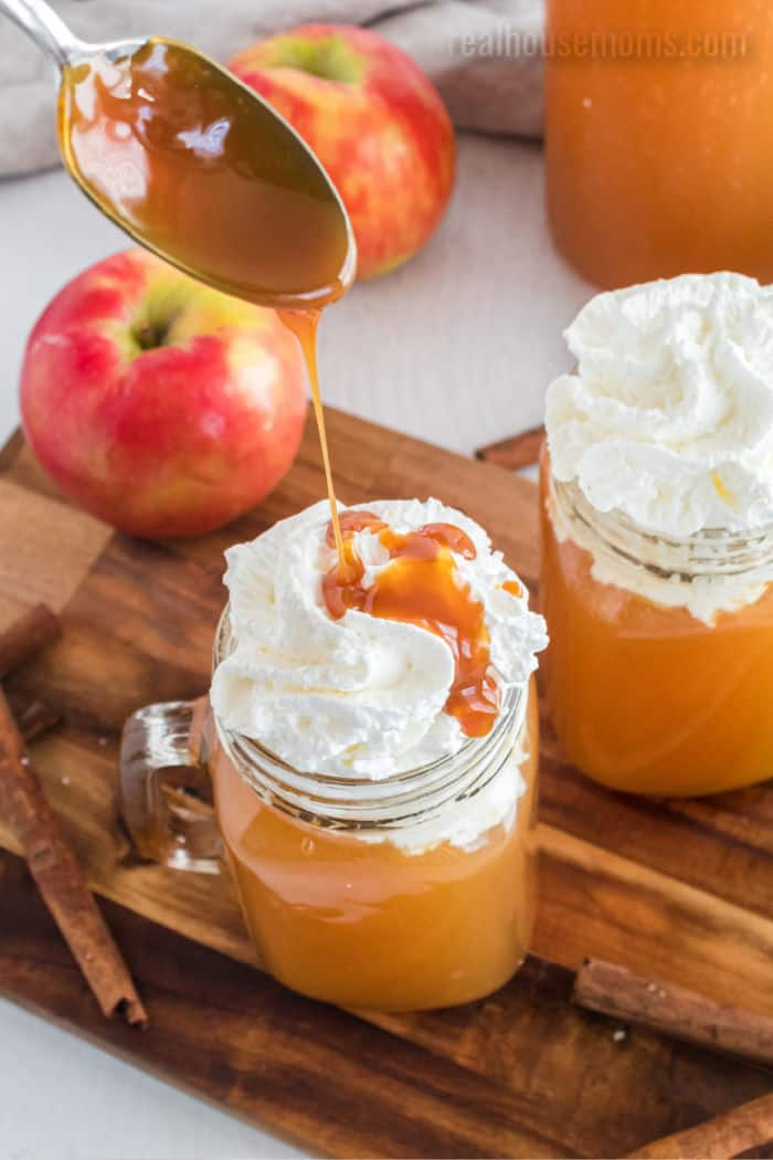 caramel being drizzled over a mug of apple cider with whipped cream on top