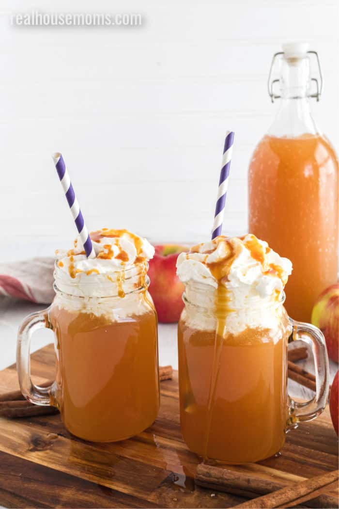 apple cider cocktail in muge with whipped cream, caramel, and straws on a wooden counter